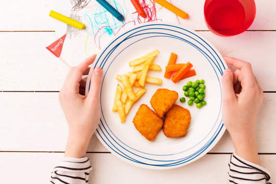 Meal (dinner) in child's hands - chicken nuggets, fries, green peas