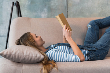 beautiful woman lying on pink sofa, smiling and reading book