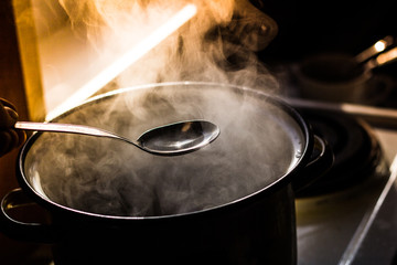 the man stirs the soup in the pan from which steam comes