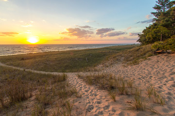Trail To The Beach. Beautiful sunset horizon with a winding sandy trail through sand dunes. Hoffmaster State Park, Michigan.