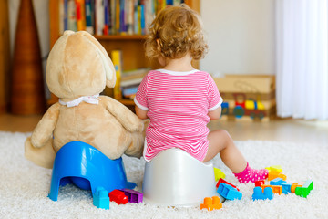 Closeup of cute little 12 months old toddler baby girl child sitting on potty. Kid playing with big plush soft toy. Toilet training concept. Baby learning, development steps