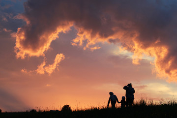 silhouette of family on wheat field at sunset