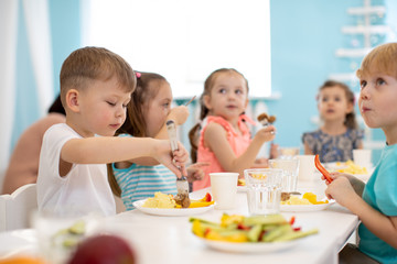 Group of kids enjoying healthy lunch in kindergarten