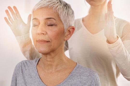 Woman having reiki healing treatment , alternative medicine concept, holistic care
