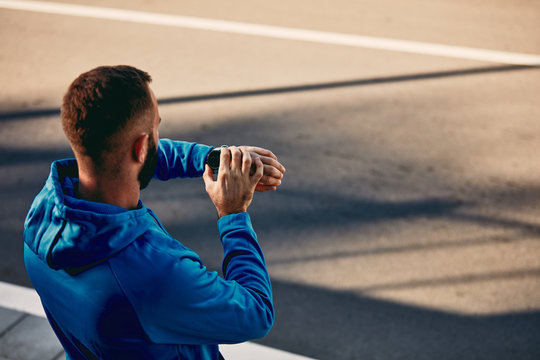 Runner setting smart watch while standing on the street. Healthy lifestyle concept. Backs turned.