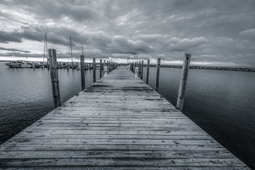 Black And Coastal Landscape. Long diminishing wooden pier on the Michigan coast.