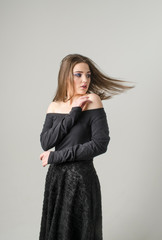 Girl in black dress on white background. Fashion portrait with beautiful girl.