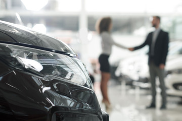 Car dealer and client shaking hands in showroom.