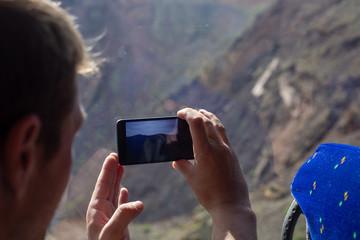 Tourist photographs the landscape through the window of a tourist bus.