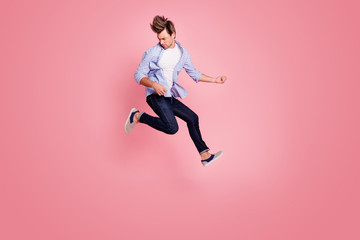 Full length body size photo of jumping high crazy he his him macho playing imagine electric guitar in arms hands hair fly wearing casual jeans checkered plaid shirt isolated on rose background