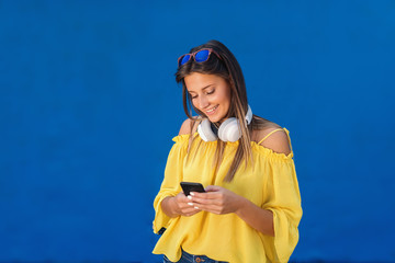 Smiling cute teenage girl in yellow blouse with sunglasses and earpieces around neck using smart phone while standing in front of blue background.
