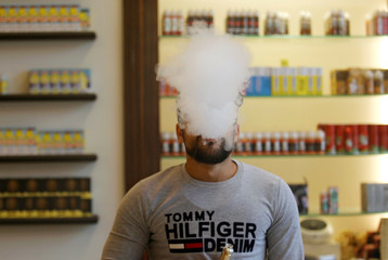 Customer vapes at a shop for electronic cigarettes in Baghdad