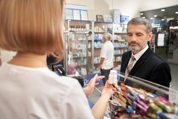 People choosing, bying medicaments in drugstore.