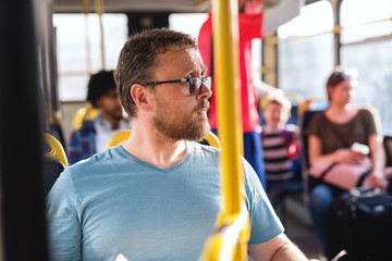 Close up of Caucasian man with eyeglasses looking away while sitting in city bus.