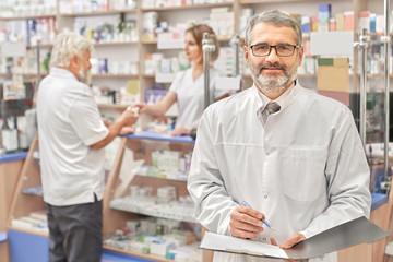 Happy chemist smiling, posing in pharmacy.