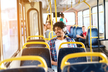 Handsome young smiling African American guy sitting in public transportation and listening to the music while looking through the window.