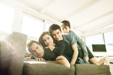Portrait of a happy, smiling family on the couch at home. United and fun family lifestyle.