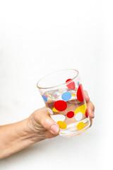 Senior woman's hand holding polka dot grass,  drinking water on white background