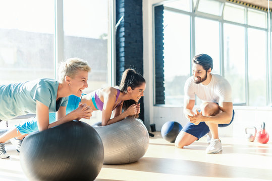 Two women smiling sporty women doing planks on pilates ball while their personal trainer kneeling and cheering for them. Gym interior.