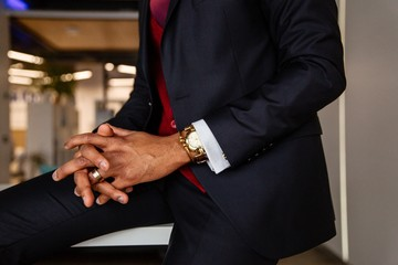 African man in a suit with a watch on his hand sits cross-fingers in the office. Hands close up