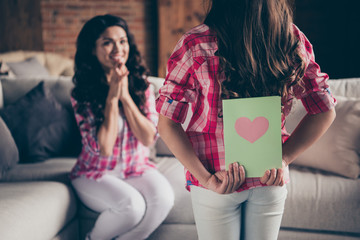 Close up back behind rear view photo two people mum little daughter giving postcard holiday morning sweet unexpected cute delighted wear pink plaid shirts flat apartment room sit cozy couch sofa divan