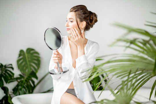 Beautiful woman taking care of her skin looking into the mirror in the bathroom with beautiful green plants. Facial skin care concept