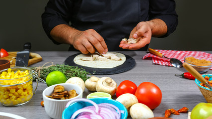 Cook preparing delicious mexican tacos with meat and vegetables at kitchen. Tasty mexican cuisine