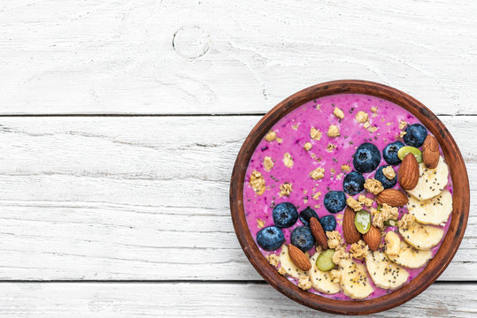 Healthy vegan breakfast. acai smoothie bowl with blueberry, fruits, granola, almonds, pumpkin and chia seeds