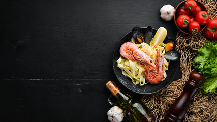 Pasta with seafood and lemon in a plate. Shrimp, mussels. On the old background. Top view. Free space for your text.