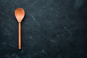 A wooden spoon on the old background. Top view. Free copy space.