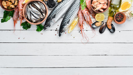Seafood on a white wooden background. Fresh fish, shrimp, oysters and caviar. Top view. Free copy space.