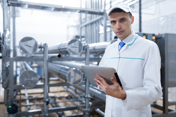 Technologist with a tablet in his hands at the dairy plant
