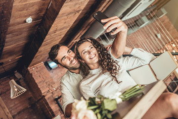Beautiful couple making selfie on new smartphone. Couple in love spends time in cafe.