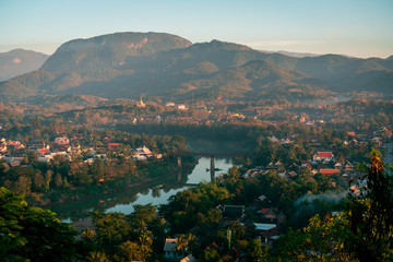 Sunset in Lunag Prabang, Laos. Beautiful clouds over the city. Mekong river between trees and houses. Winter in Laos