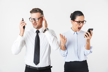 Angry screaming business colleagues couple isolated over white wall background talking by mobile phones.