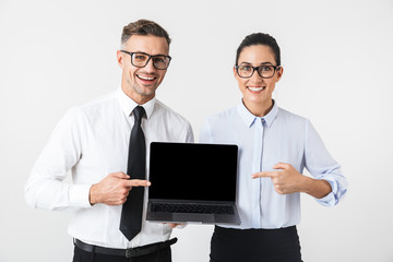 Business colleagues couple isolated over white wall background using laptop computer.