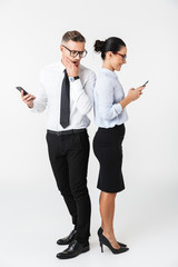 Business colleagues couple using mobile phones isolated over white wall background.