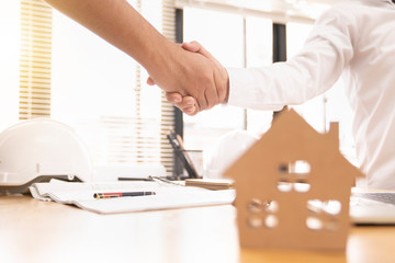 architect or civil engineer  and client or customer shaking hands for agreement of home or building plan,plan is fake only for stock photo.