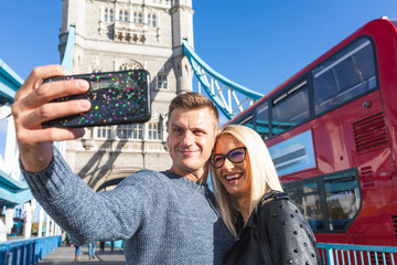 Happy couple tourists taking selfie at Tower Bridge in London