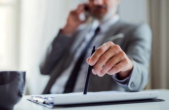 A midsection of businessman with smartphone sitting at the table, making a phone call.