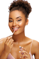 Charming young girl using lip gloss. Photo of smiling african american girl on white background. Beauty concept