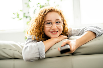 child watching tv on the sofa at home alone