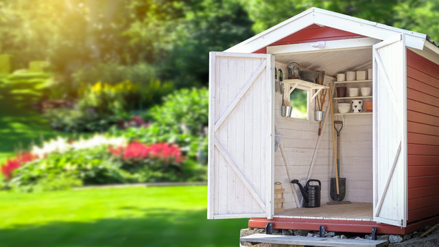 Storage shed filled with gardening tools. Beautiful green botanical garden in the background. Copy space for text and product display.