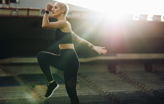 Female athlete doing warm up exercises in a stadium