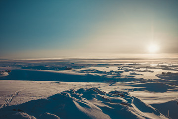 Bright sunrise panorama of the Antarctica. Overwhelming polar landscape. The winter sun over the snow covered frozen land. Ideal background for the collages and illustrations. Antarctic South Pole