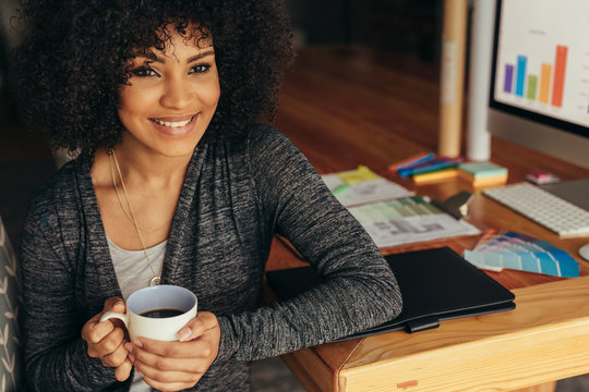 Happy woman having coffee at home office desk