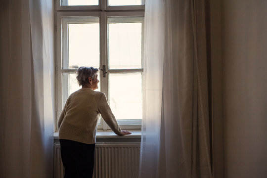 A portrait of a senior woman standing at home, looking out of a window.