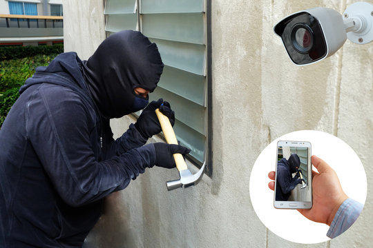 Surveillance Camera capture and record caught Masked thief with hammer and hand holding Mobile Phone Detecting on application, home Security System