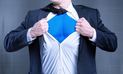 Businessman tears shirt on himself to show that he is Superman