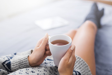 Woman resting in bed with cup of tea
